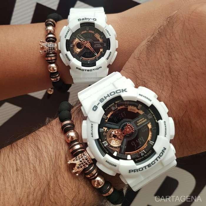 Se venden relojes Casio blancos con fondo negro y cobrizo para pareja