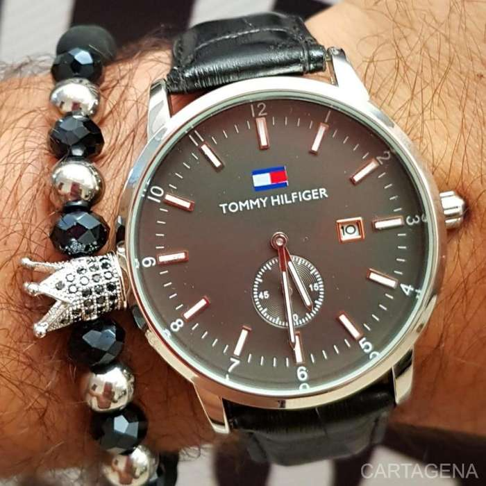Reloj Tommy negro y plateado con el fondo negro para hombre