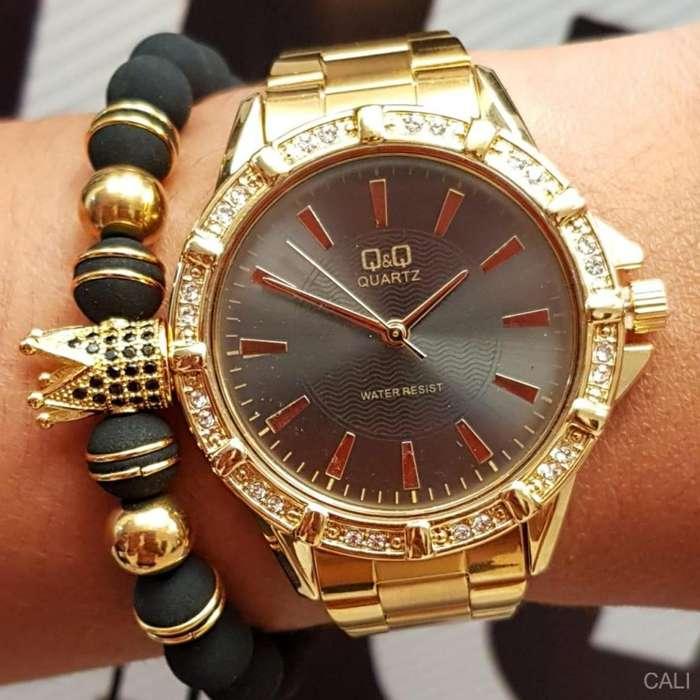 Reloj Q&Q para dama dorado con fondo oscuro