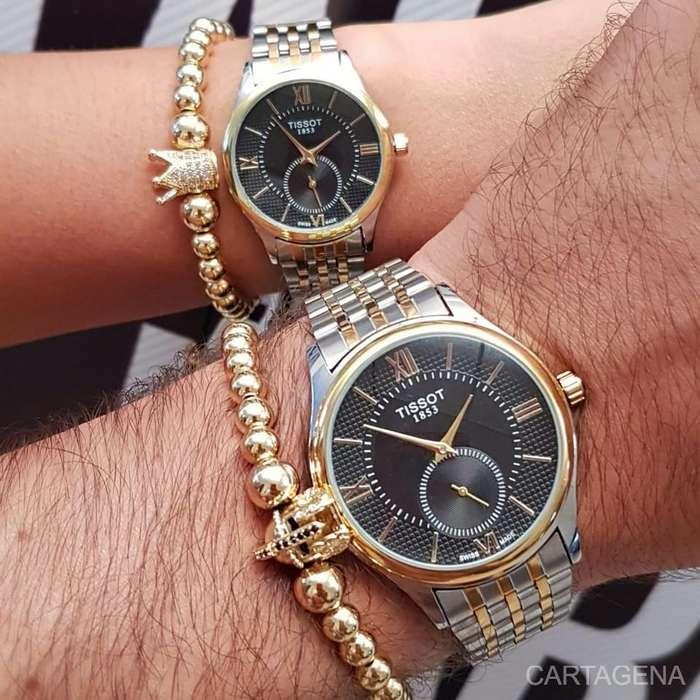 Se vende Tissot para pareja en color dorado y plateado con el fondo de color negro y cronografos