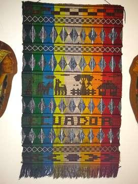 Tapiz artesanal y figuras de indígenas de madera pintada a mano