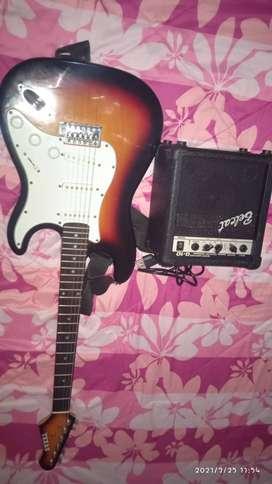 Guitarra eléctrica con amplificador mediano.