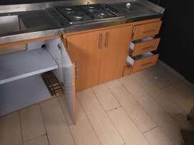 Mueble en ele de cocina en acero con estufa empotrada