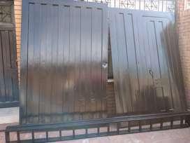 Vendo Portón metálico pesado, en buen estado, para garaje, bodega o  local.