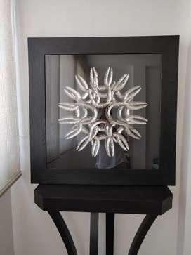Cuadro decorativo con figura metálica, marco de madera y vidrio protector.