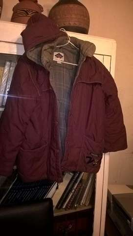 Campera Impermeable talle 8 Niño muy abrigada color bordó con broches y capucha desmontable, dos bolsillos .