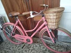 Bicicleta vintage rod 26 rosa con canasto de mimbre.