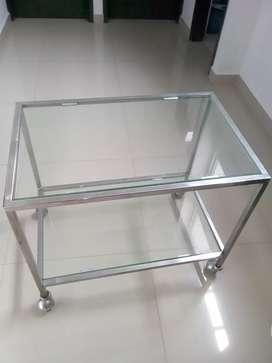 vendó mesa en acero y vidrio con rodachines.GANGA.