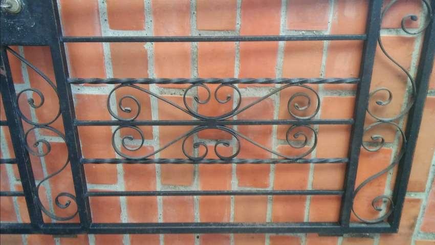 vendo puerta reja en muy buen estado con barras de acero entorchado y cerradura con llave color negro