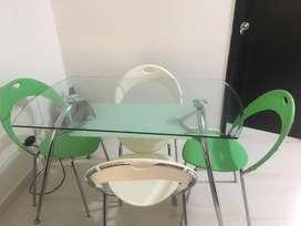 Mesa comedor en vidrio 4 puestos, 2 sillas blancas, 2 sillas verdes.