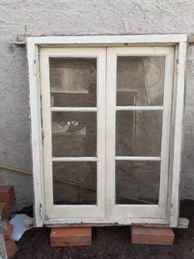Vendo ventana de cedro pintada con marco vidrios fume y postigos
