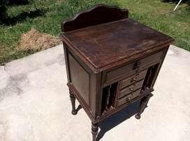 Mesa de luz antigua con un cajón grande y tres chicos más revistero