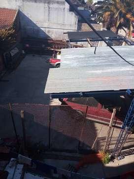 Cochera techada con piso de hormigón y cortina metálica motorizada