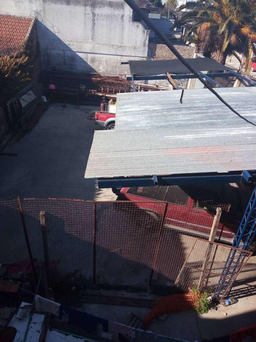 Cochera techada con piso de hormigón y cortina metálica motorizada 0