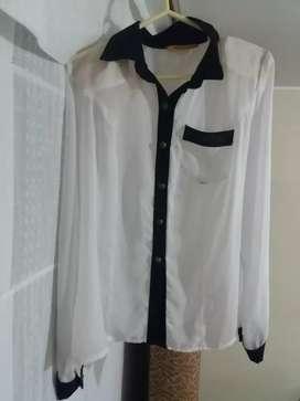 Blusa color blanco con mangas y cuello negro, botones color oro viejo y bolsillo