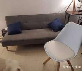 Sofá cama gris con silla blanca