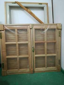 Dos ventanas nuevas de dos hojas con vidrios repartidos y postigones en madera de eucaliptus.