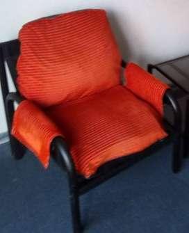 Juego de sillones individuales de caño con almohadones rojos
