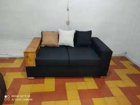 Sofá  con terminados en madera. Y tela