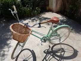 Bicicleta color verde agua, con canasto de mimbre, ruedas blancas.
