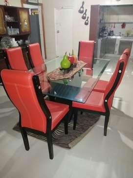 Juego de Comedor de 6 puestos, con mesa de vidrio fuerte y pesado. Sillas en maderas con tapizado rojo.