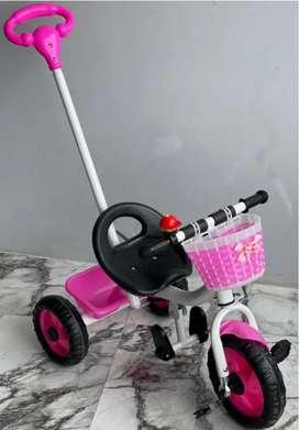 Triciclo color branco y negro para  niños con barra de empuje y canasta  trasera.