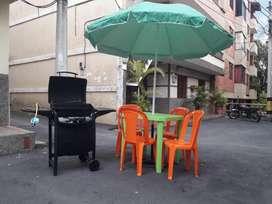 Asador a gas y mesa de jardín con sombrilla y sillas