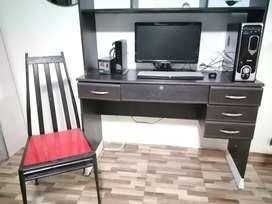 Computador de escritorio con impresora y mueble.