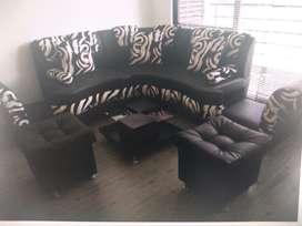 Mueble de sala esquinero en perfecto estado con dos puff y mesa de centro.